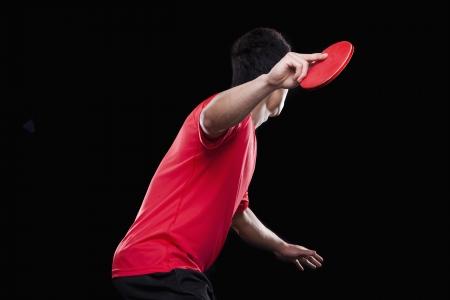 jugando tenis: Hombre jugando al ping pong, fondo negro