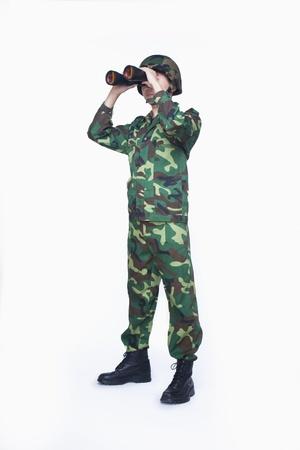 Man in military uniform using binoculars Stock fotó