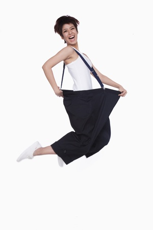 oversized: Girl in oversized pants jumping Stock Photo