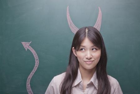 cola mujer: Mujer joven con cuernos de diablo y la cola en la pizarra