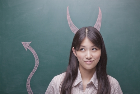 devil horns: Young woman with devil horns and tail on blackboard