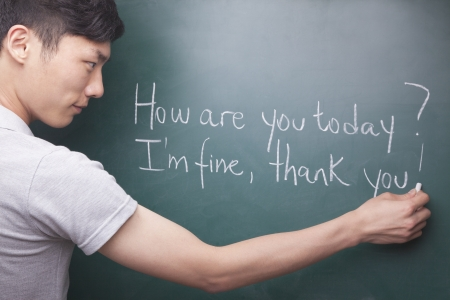 english ethnicity: Young man writing English sentences on the blackboard