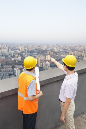 Architect And Construction Worker Talking On Rooftop Stock Photo - 21121404