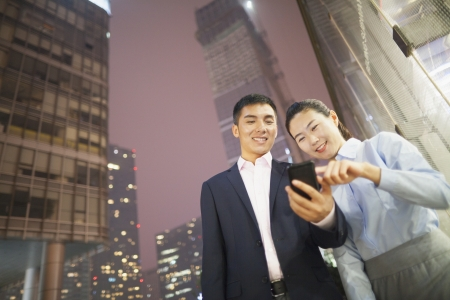 two business people smiling and looking at the phone  Imagens