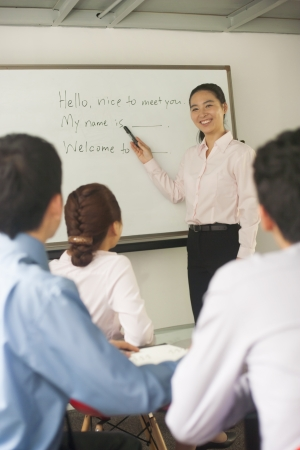 coworkers: Office worker teaching coworkers  Stock Photo