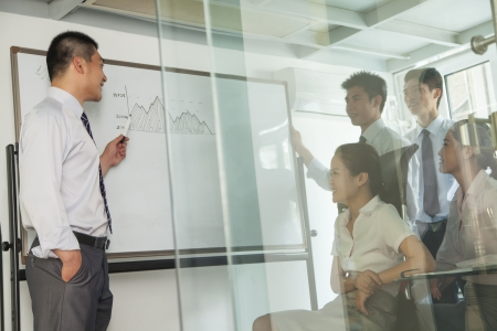 Workers looking on the diagram on the whiteboard Imagens