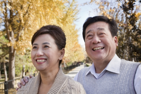 55 59 years: Happy Mature Couple Enjoying the Park in Autumn Stock Photo