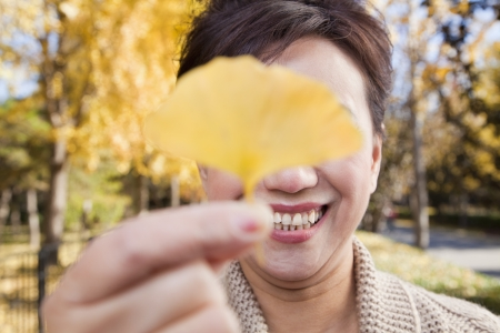 55 59 years: Mature Woman Covering Her Eyes with Yellow Ginkgo Leaf