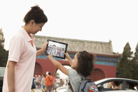 generation gap: Mother and daughter with digital tablet