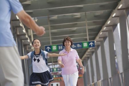 three generation: Granddaughter running towards her grandfather Stock Photo