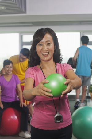 Woman holding ball on foreground, people working out in the gym on the background photo
