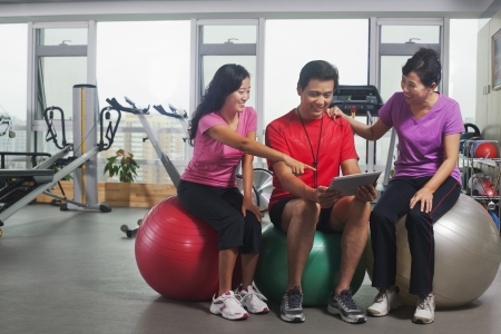 personas mirando: Las personas que buscan en la tableta digital en el gimnasio