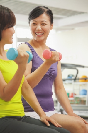 self conscious: Two mature women lifting weights in the gym  Stock Photo