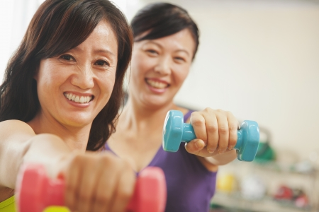 self conscious: Two mature women lifting weights in the gym and looking at the camera