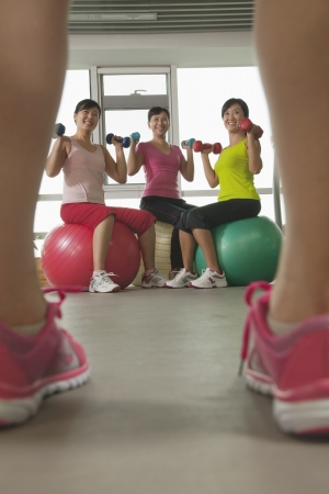 mature women exercising with fitness ball and looking at the trainer photo