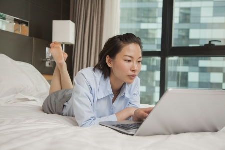Businesswoman working on her laptop in the bed photo