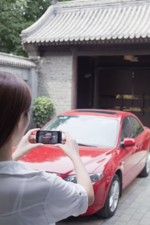 Young Woman Taking a Picture of Her Car