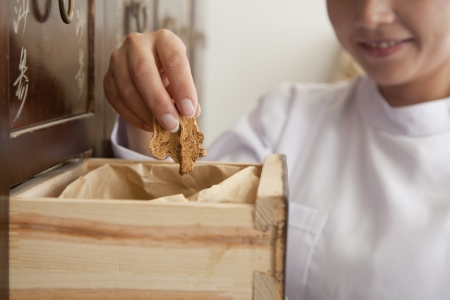traditional medicine: Doctor Taking Herb Used for Traditional Chinese Medicine Out of a Drawer