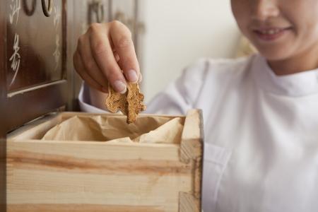 medicina tradicional china: El doctor Taking hierba usada para la Medicina Tradicional China de un caj�n