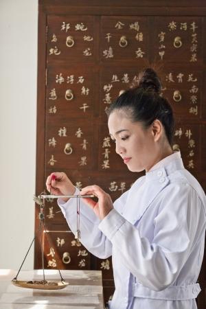 medicina tradicional china: Doctor que pesa a la medicina herbaria con escala