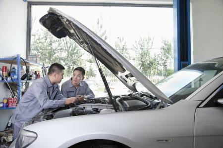 Two Garage Mechanics Working on Engine Stock Photo
