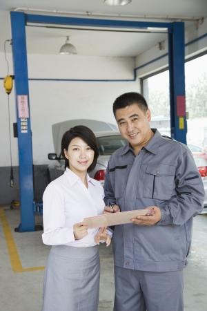 explaining: Garage Mechanic Explaining to Customer Stock Photo