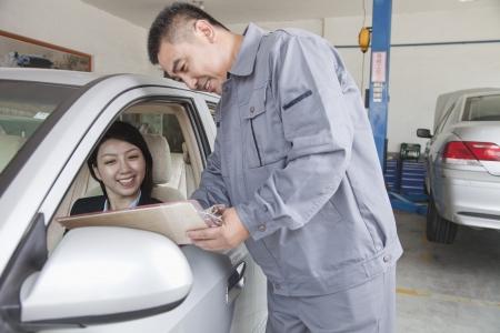 explaining: Mechanic Explaining to Businesswoman