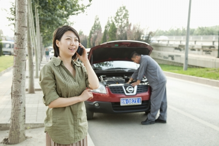 Woman Talking on Phone While Mechanic Fixes Her Car photo