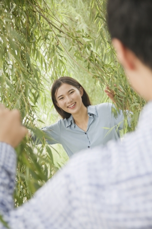 Couple Looking Through Willow Branches photo