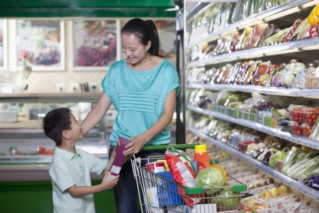 three shelves: Mother and son shopping for groceries in supermarket, Beijing
