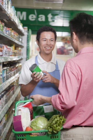 sales clerk: Sales clerk assisting man in supermarket, Beijing