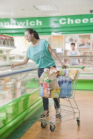 Woman shopping in supermarket, looking down in refrigerated section, Beijing Stock Photo - 21121727