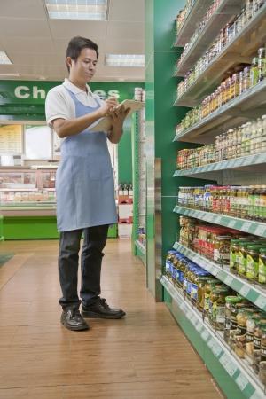 Sales clerk checking merchandise in supermarket photo