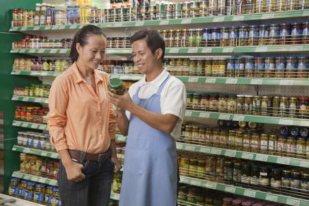 three shelves: Sales clerk assisting women, examining jar in the supermarket, Beijing Stock Photo