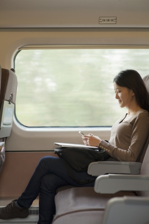 Young woman sitting on a train using her phone Stock Photo - 21121768