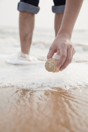 human leg: Close up on hand holding seashell Stock Photo