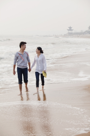 waters  edge: Young couple walking by the waters edge on the beach, China