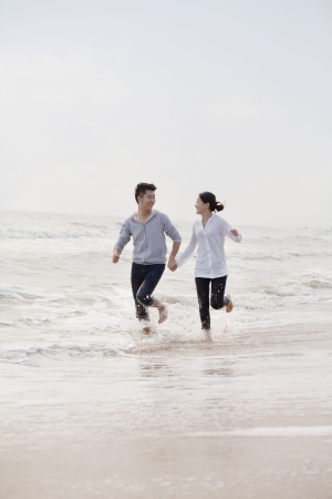 waters  edge: Young couple holding hands running by the waters edge on the beach, China