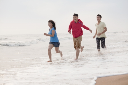 away from it all: Three friends running on the beach by the waters edge, China Stock Photo