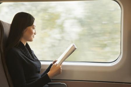 on train: Mujer joven leyendo una revista mientras viaja en el tren