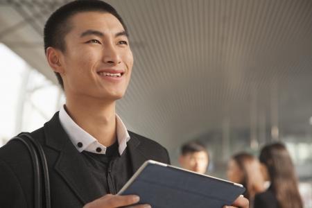 Young Man Using Digital Tablet on Train Platform photo