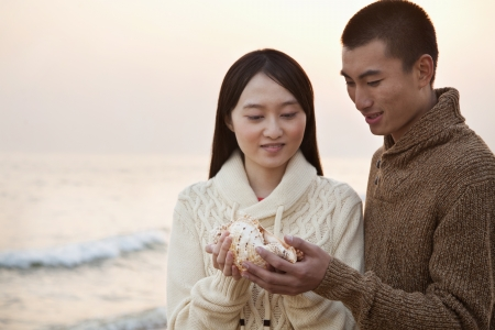 Young Couple Looking At a Seashell Imagens - 35986242