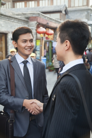 Two young businessman handshaking in houhai, Beijing, China Imagens
