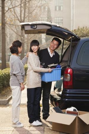 Family unpacking minivan for college, Beijing photo