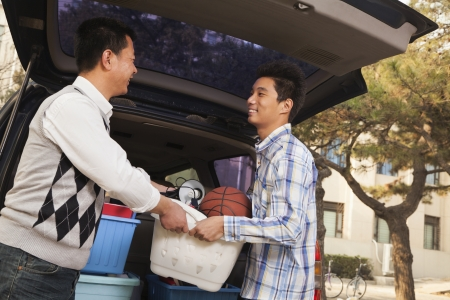 Father and son unpacking car for college Stock Photo