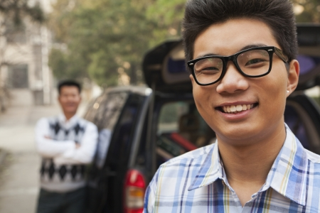 Portrait of boy in front of car on college campus photo