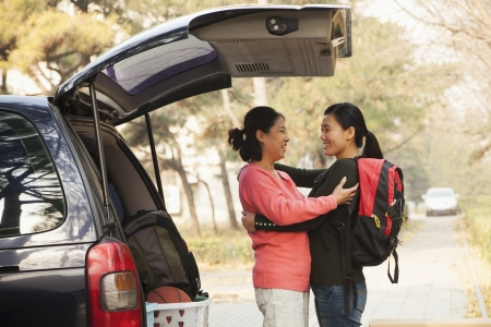 college basketball: Mother and daughter embracing behind car on college campus Stock Photo