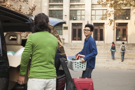 dormitory: Young man moving into dormitory on college campus Stock Photo