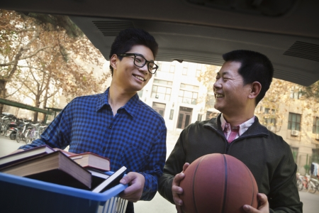 Father and Son in back of car in front of dormitory photo