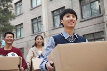 Family moving boxes into a dormitory at college Stockfoto